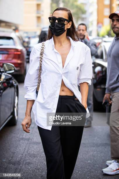 Irina Shayk, wearing a white shirt and black pants, poses ahead of the Max Mara fashion show during the Milan Fashion Week - Spring / Summer 2022 on...