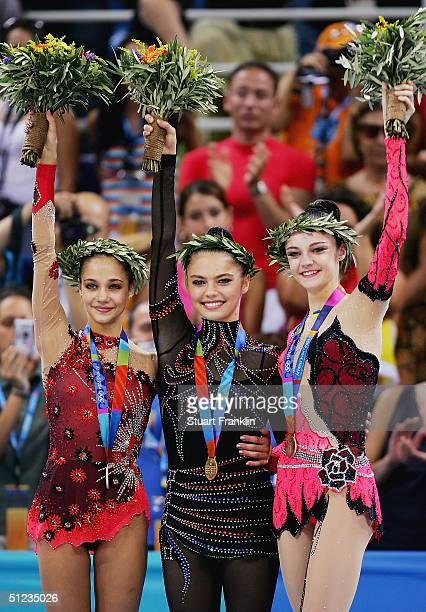 Irina Tchachina of Russia Alina Kabaeva of Russia and Anna Bessonova of the Ukraine acknowledge their support during the medal ceremony for rhythmic...