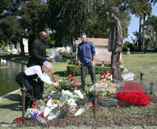 Irina Yelchin actor Anton Yelchin's mother places flowers at the foot of her son's memorial statue as sculptor Nick Marra looks on at the Anton...