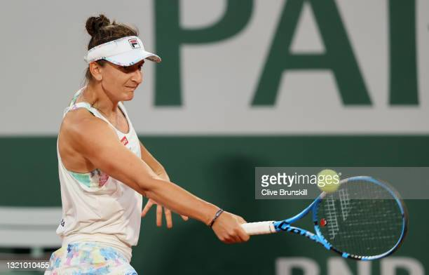 Irina-Camelia Begu of Romania plays a backhand in their ladies singles first round match against Serena Williams of The United States on day two of...