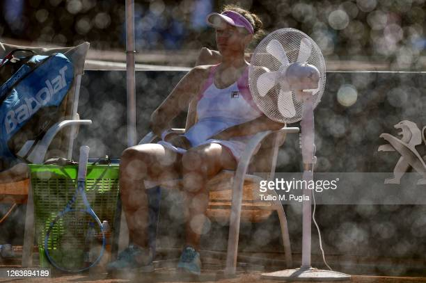 Irina-Camelia Begu of Romania takes a break as water is sprayed on the pitch during her match against Laura Siegemund of Germany during the 31st...
