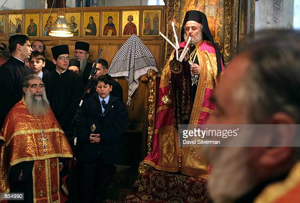 Irineos I GreekOrthodox Patriarch of the Holy Land holds candles as he leads Mass January 6 2002 in the Church of the Nativity in biblical Bethlehem...