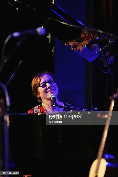 Iris DeMent's face is reflected on the piano top whe she performs at City Winery on November 15 2015 in New York City