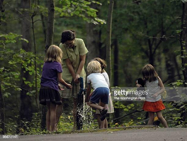 Iris Diaz-Sliker pumps for water with the kids Martha Spletzer left, Roger Spletzer center, Iris's four year old daughter, center rear, and Roger's...