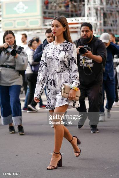 Iris Law wears earrings, a white long sleeves mini dress with grey and black horses drawings print, a beige bag with a colorful chain handle, black...