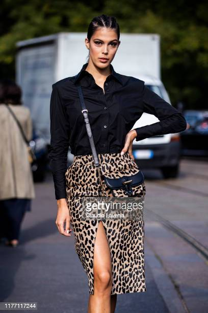 Iris Mittenaere, wearing a black shirt, leopard print midi skirt, black studded Tod's loafers and leopard print Tod's bag, is seen outside the Tod's...