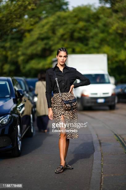 Iris Mittenaere wears earrings, a black shirt, a beige and black leopard print front-split skirt, a beige and black leopard print crossbody bag,...