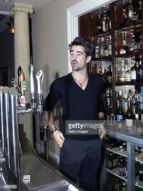 Irish actor Colin Farrell pulls pints behind the bar at Renards Night Club March 10 2003 in Dublin Ireland