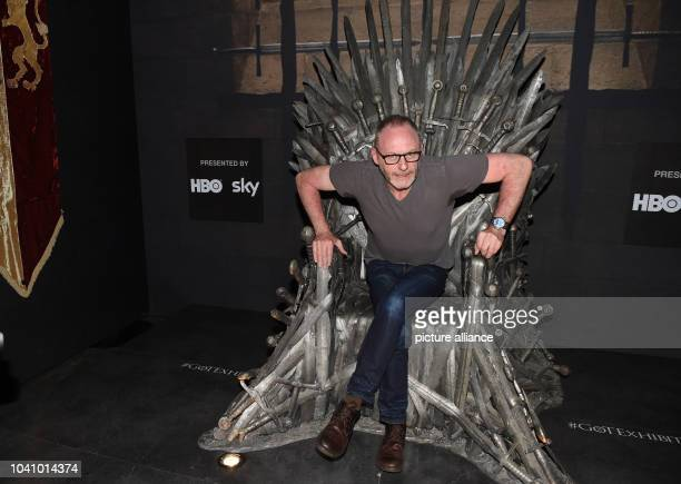 Irish actor Liam Cunningham poses on the 'Iron throne' a prop of the US television show 'Game of Thrones' on display during the preopening event of...