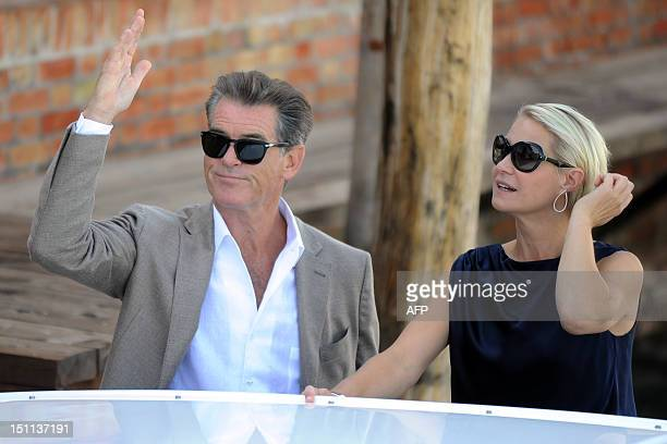 Irish actor Pierce Brosnan and Danish actress Tryne Dyrholm wave from a boat on their way to Venice Lido during the 69th Venice Film Festival on...