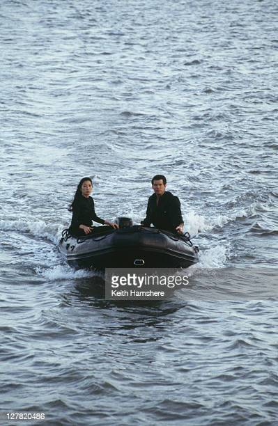 Irish actor Pierce Brosnan as 007 with Malaysian actress Michelle Yeoh as Wai Lin in a motorised rubber dinghy whilst on location for the James Bond...