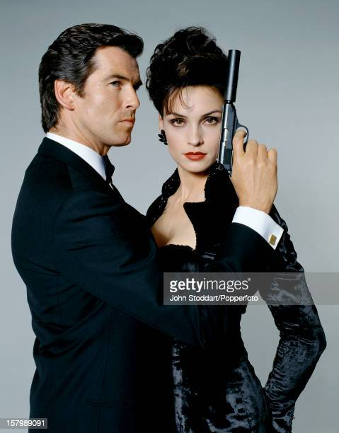 Irish actor Pierce Brosnan as James Bond with his 'GoldenEye' costar Famke Janssen 1995 He is holding a Walther PPK with a silencer