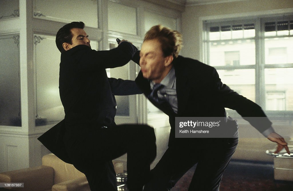 Irish actor Pierce Brosnan deals with a henchman in the offices of a Swiss banker, in the opening sequence of the James Bond film 'The World Is Not Enough', 1999.