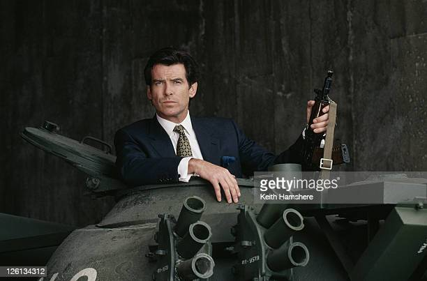 Irish actor Pierce Brosnan poses in the hatch of a Russian T55 Main Battle Tank holding a Kalashnikov automatic rifle, in a publicity still for the...
