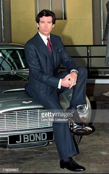 Irish actor Pierce Brosnan poses on the bonnet of an Aston Martin DB5 during a publicity shoot for the James Bond film 'GoldenEye' 22nd January 1995
