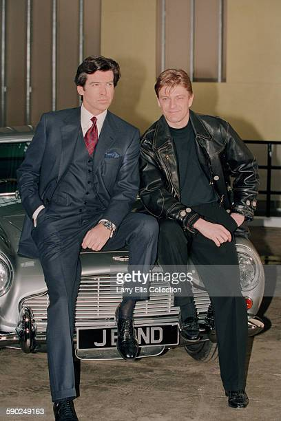 Irish actor Pierce Brosnan poses with hiscostar Sean Bean on the bonnet of an Aston Martin DB5 with the numberplate 'JBOND' during a publicity shoot...