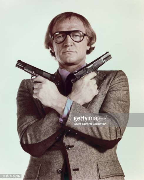Irish actor Richard Harris as hit man Harry Crown, wielding his two Browning Hi-Power 9mm pistols in a publicity still for the action comedy film '99...