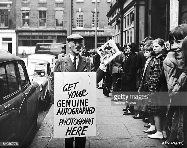 Irish actor Wilfrid Brambell wears a sandwich board advertising 'Genuine Autographed Photographs' in a still from the Beatles film 'A Hard Day's...