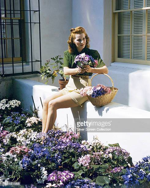 Irish actress Maureen O'Hara picking flowers in a garden circa 1940