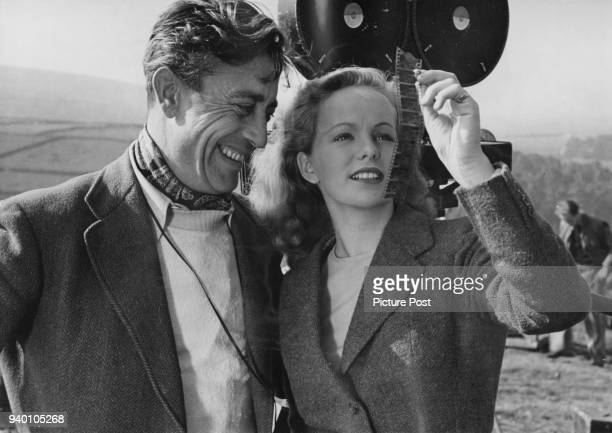 Irish actress Peggy Cummins examines a length of film stock with cinematographer Freddie Young during the filming of 20th Century Fox's 'Escape' in...
