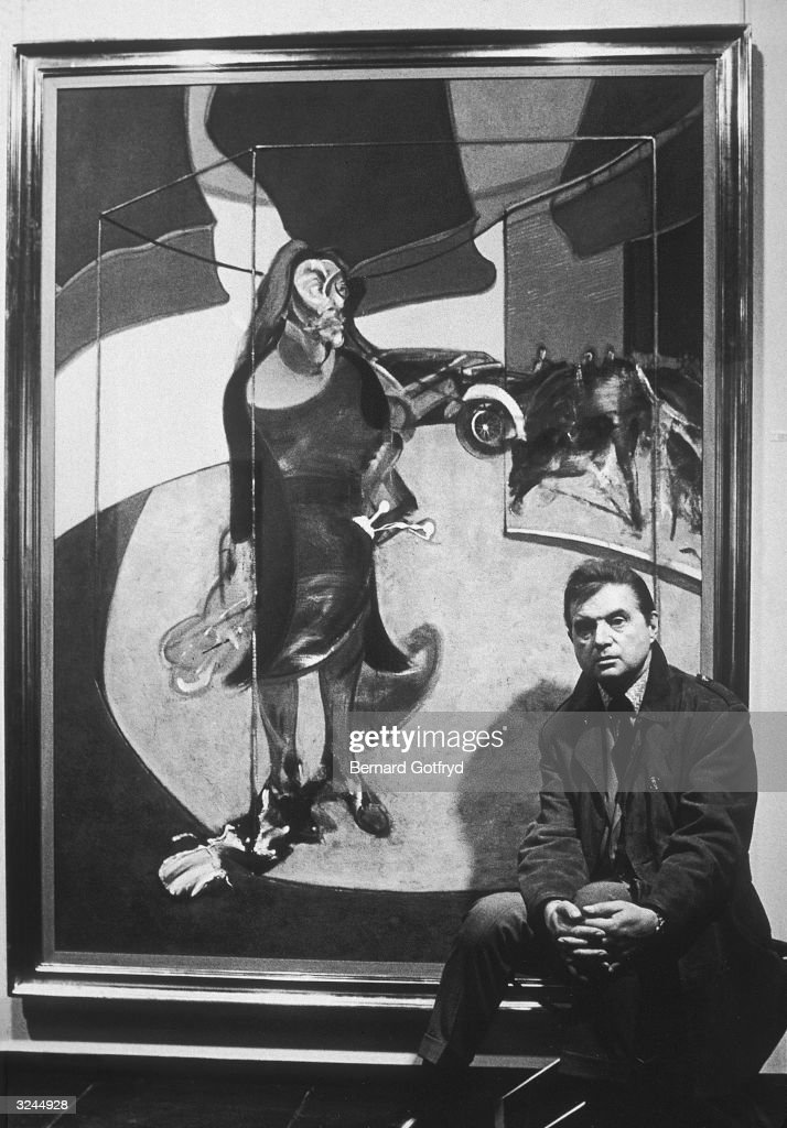 Irish artist Francis Bacon (1909 - 1992) sitting in front of one of his paintings.