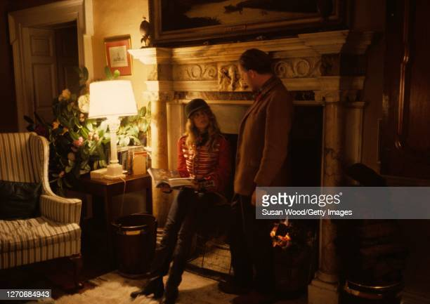 Irish author and conservationist Desmond Guinness talks with his daughter Marina Guinness dressed in a jacket and leaning against a fireplace screen...
