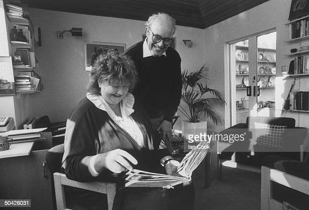 Irish author Maeve Binchy looking at a photo album as she sits in a chair while her husband writer Gordon Snell looks on over her shoulder at home