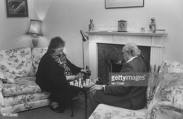 Irish author Maeve Binchy playing chess w her husband writer Gordon Snell in living room at home
