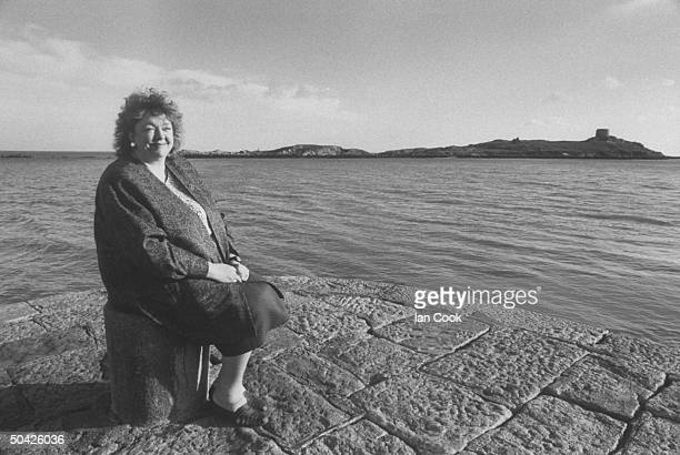 Irish author Maeve Binchy posing on jetty at the edge of the sea nr her home