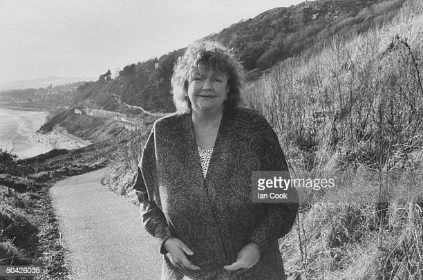 Irish author Maeve Binchy posing on road at the edge of the sea nr her home