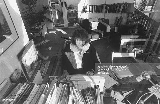 Irish author Maeve Binchy sitting at desk using computer to work on novel at home
