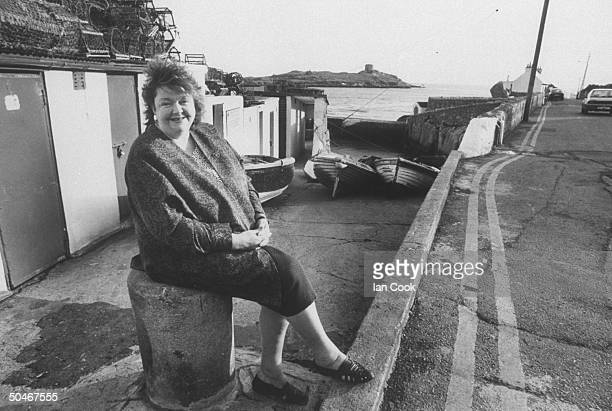 Irish author Maeve Binchy sitting on piling nr small row boats on road next to the sea nr her home
