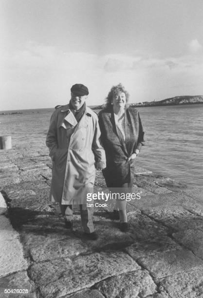 Irish author Maeve Binchy walking along sea jetty w her husband writer Gordon Snell