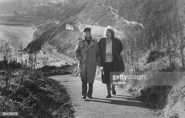 Irish author Maeve Binchy walking w her husband writer Gordon Snell on road next to the sea