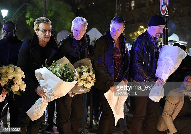 Irish band U2 lead singer Bono bass player Adam Clayton drummer Larry Mullen Jr and guitarist The Edge pay homage to attacks' victims near the...