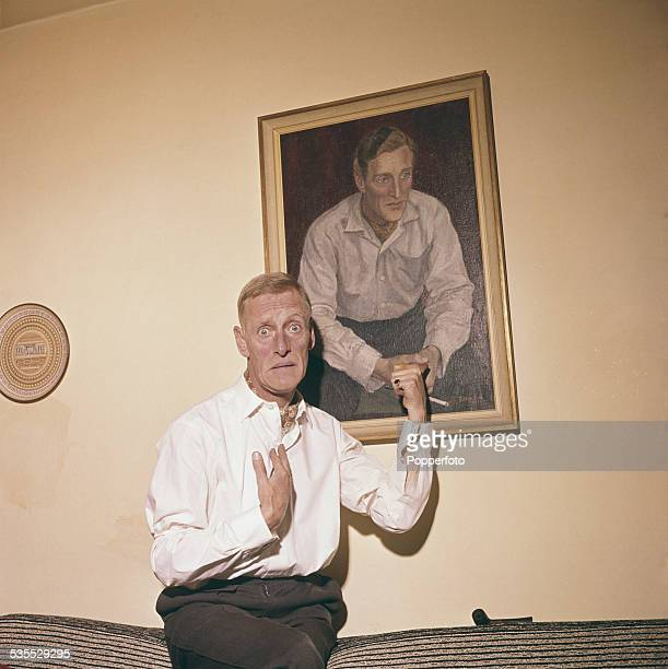 Irish born actor Wilfrid Brambell who plays Albert Steptoe in the television sitcom 'Steptoe and Son' posed at home in front of a portrait of himself...