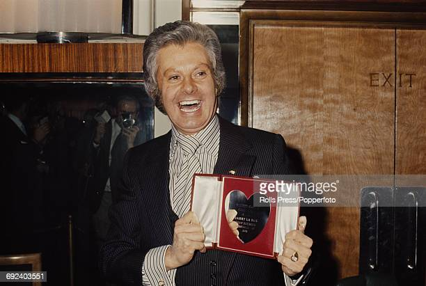 Irish born British entertainer Danny La Rue pictured holding his Variety Club of Great Britain Showbusiness Personality of the Year award in London...