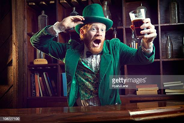 irish character / leprechaun celebrating with pint of beer - st patricks stock pictures, royalty-free photos & images