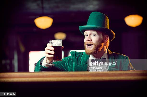 irish character / leprechaun toasting with a pint of beer - st patricks day stock pictures, royalty-free photos & images