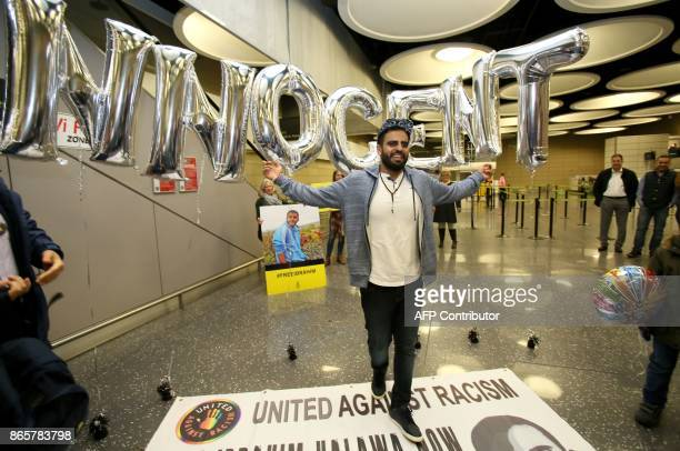 Irish citizen Ibrahim Halawa poses in front of balloons spelling the word 'Innocent' as he arrives at Dublin Airport on October 24 2017 following his...