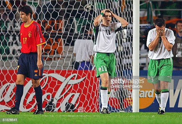 Irish defender Ian Harte and teammate Kevin Kilbane react to Harte's failure to convert a penalty try as Spain's Juan Carlos Valeron shows his relief...