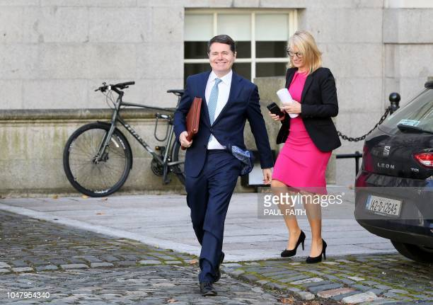 Irish Finance Minister, Paschal Donohoe carries a copy of the 2018 budget as he arrive for a photocall in front of the Government Buildings in...