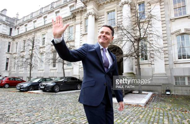 Irish Finance Minister Paschal Donohoe gestures as he emerges from his office for a photo call prior to presenting his Budget 2020 to parliament at...