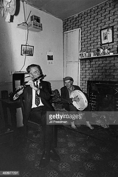 Irish flute player Packie Duignan and Bodhran player Pat Phildy McGowan play their instruments by the fireplace Ireland circa 1974