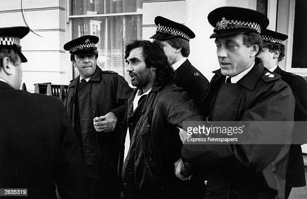 Irish footballer George Best is led away by policemen. He was later accused of drunk driving and assaulting a police officer.