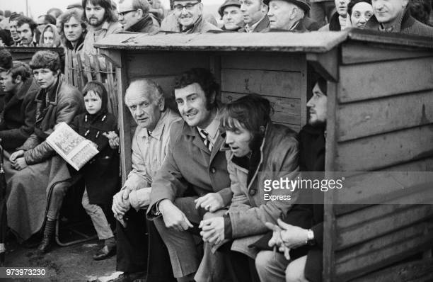 Irish former footballer and manager of Reading FC, Charlie Hurley pictured 2nd from left with trainer Jimmy Wallbanks in the dugout during a match in...