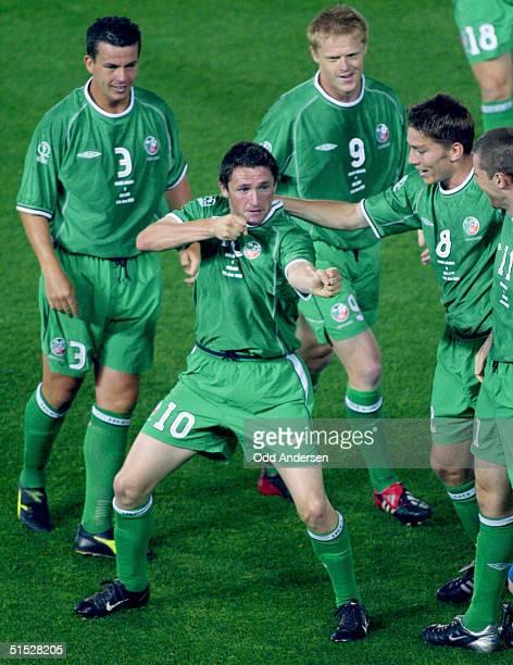 Irish forward Robbie Keane is congratulated by his teammates defender Ian Harte, forward Damien Duff , midfielder Matt Holland and forward Kevin...