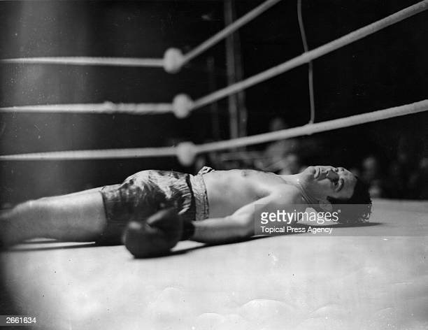 Irish heavyweight boxer Jack Doyle on the ring floor after being knocked down in the first round of his fight against Eddie Phillips at White City...