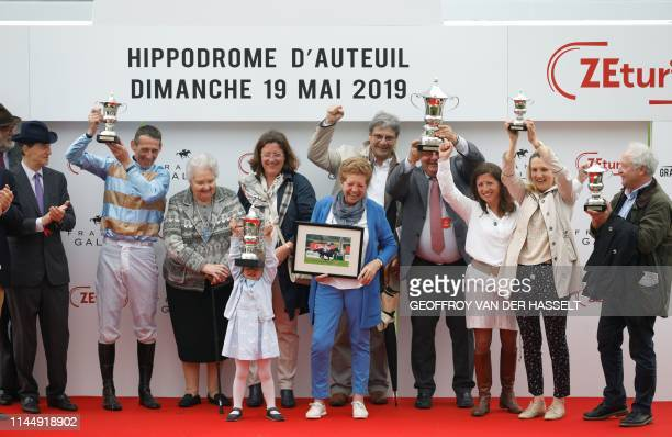 Irish jockey Davy Russell and Isabelle Pacault the trainer of his horse Carriacou pose on the podium as President of France Galop Edouard de...