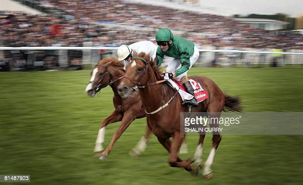 Irish jockey Kevin Manning rides the horse New Approach across the finish line to win the 2008 Derby Festival at Epsom Downs race course, 20kms south...